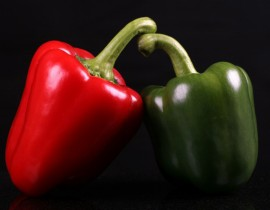 red and green peppers on black still life photography